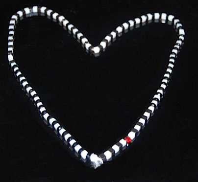 black and white necklace with one red bead.