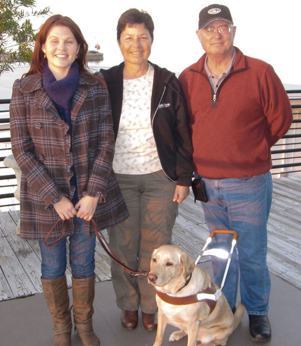 Barbara and Jerry Edwards stand smiling with Doris and her handler Rebecca in New Orleans.