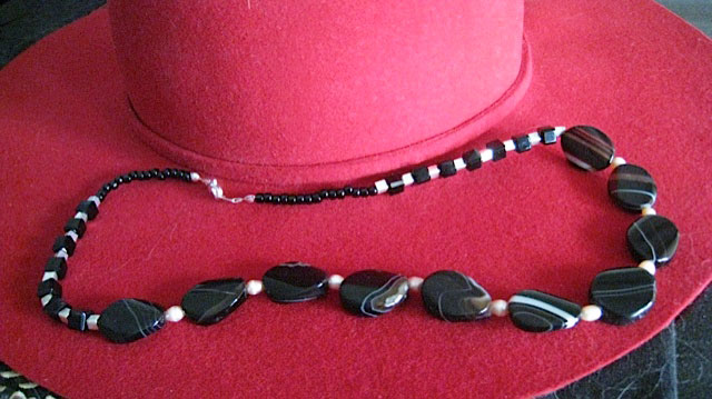 necklace of black onyx ovals with thin white lines in them and silver and black square beads.