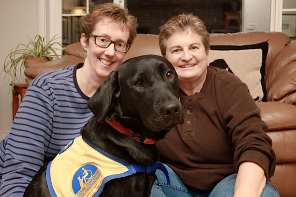 Shiny black Lab puppy Flurry in her yellow and green CCI jacket sits happily on the couch between smiling co-raisers Kathy Ulm and Gloria Merk.